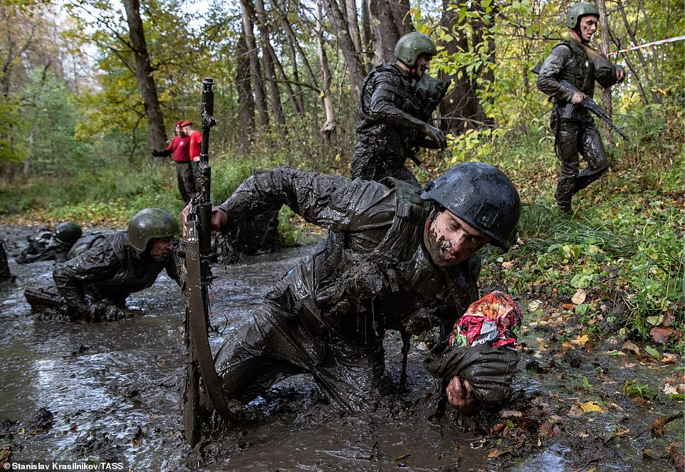 Soldiers caked in dirt crawl through thick mud carrying rifles. A 'psychological manipulation' group are employed to follow them and test their mental durability