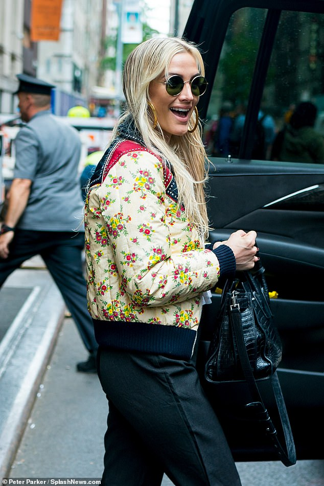 Snappy: Ashlee, 34, slipped into a splashy floral jacket with navy and red bordering, slinging a black snakeskin leather purse over one forearm