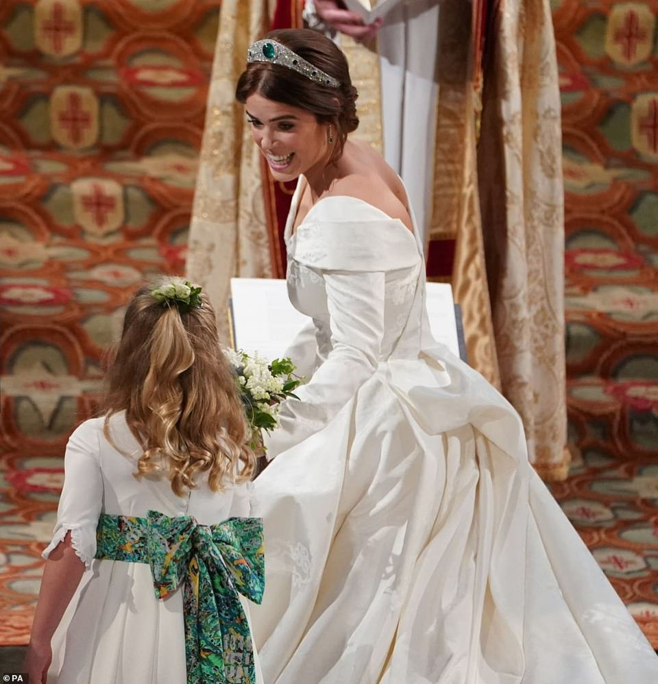Glowing bride Princess Eugenie smiled as she looked back to hand her bouquet to one of her young bridesmaids