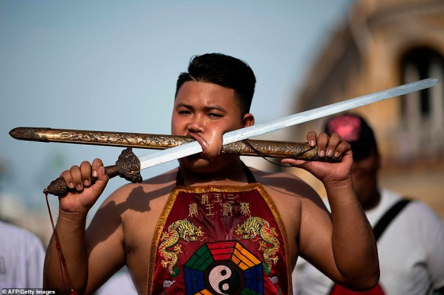 Full use: A young man has pushed both the ceremonial sword and the weapon's cover through his cheek