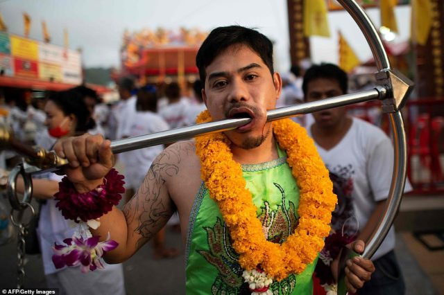 A devotee of the Loem Hu Thai Su shrine has a metal rod pierced through his cheek during the annual Vegetarian Festival