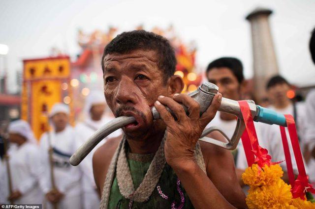 Modern pain: A man is seen walking down the street witha gas-pump nozzel pierced through his cheek