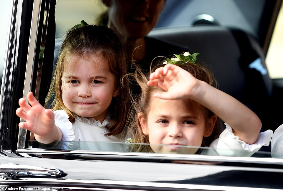 We've arrived, everyone! Princess Charlotte and Theodora Williams were eager to make their presence felt as they peered out the window and waved to the crowds on arrival at St George's Chapel