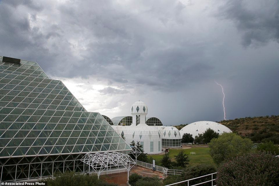 In this July 31, 2015 photo, several of the main buildings of the Biosphere 2 complex, including the tropical rainforest, left, the technosphere, middle, and the south lung, right, are shown as a thunderstorm moves past, in Oracle, Ariz. University of Arizona officials say that 25 years after that New Age-style experiment in the Arizona desert, the glass-covered greenhouse thrives as a singular site for researchers from around the world studying everything from the effects of the ocean's acidification on coral to ways of ensuring food security.