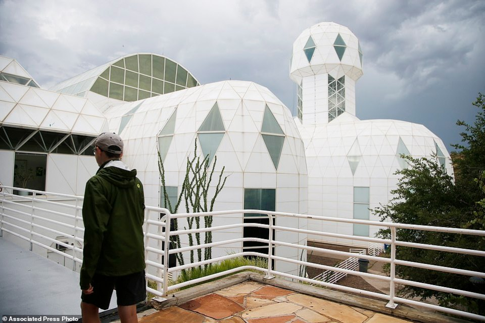 A tourist walks to the main entrance of the Biosphere 2 facility while on a walking tour in Oracle, Ariz