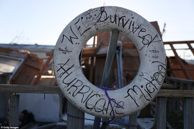 A sign written on a life preserver ring reads: 'we survived hurricane Michael'