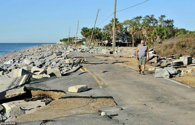 Mike Lester walks along the washed out road in front of his home on the Gulf of Mexico in the aftermath of Hurricane Michael