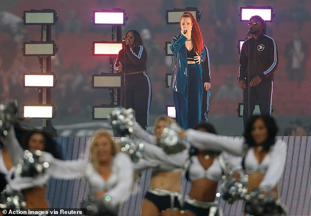 Cheerleaders dance in front of Glynne as she performs on Sunday evening