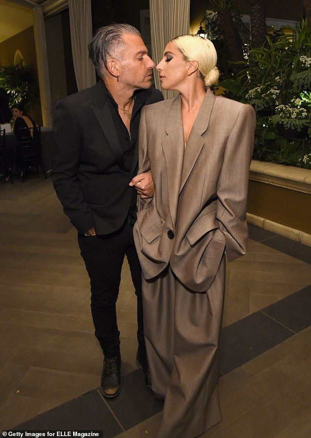 Cute couple:On the red carpet, Gaga was accompanied by fiancé Christian Carino, 49, and the pair puckered up for a kiss as photographers snapped away