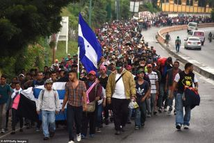 Migrants with the Honduran flag take part in a caravan towards the United States in Chiquimula, Guatemala on Wednesday