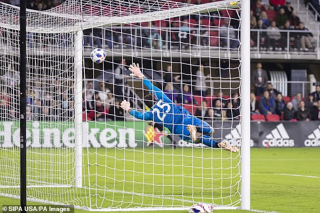 Toronto FC goalkeeper Alex Bono dives helplessly as he can't get anywhere near Rooney's shot