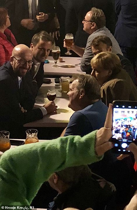After the summit meeting last night (clockwise around the table from back right) French President Emmanuel Macron, German Chancellor Angela Merkel, Belgian PM Charles Michel and Luxembourg PM Xavier Bettel went out for drinks at a bar in Brussels