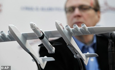 Microsoft co-founder Paul Allen looks across at a model of a giant airplane and spaceship.Allen died Monday in Seattle from complications of non-Hodgkin's lymphoma, aged 65.