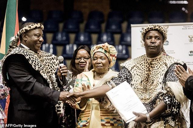 South African President Cyril Ramaphosa (far left) hands over the title deeds of 4,586 hectares of land to Inkosi (Chief) Mandla Mkwanazi of the KwaMkwanazi community in Empangeni near Durban