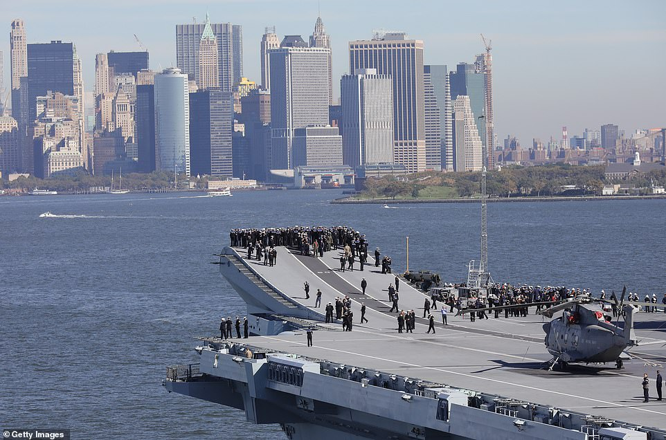 Hundreds of sailors and officers are pictured taking in the views on HMS Queen Victoria's deck in New York Harbor