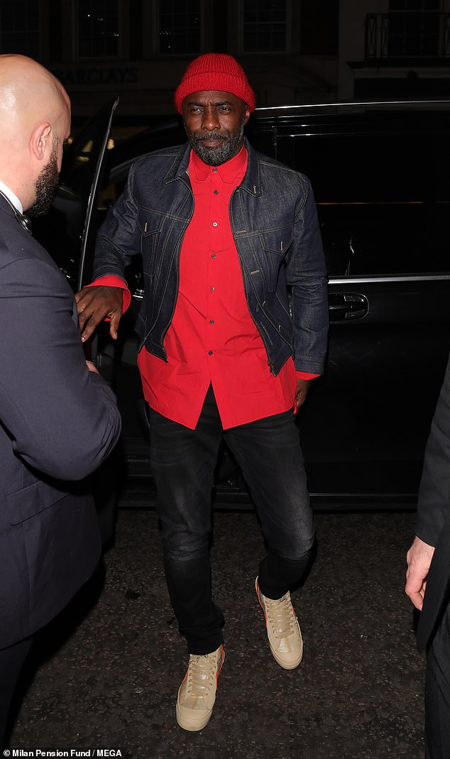 On the scene: Idris looked suave in his bright red shirt matched with his scarlet beanie as he made his grand arrival at the glitzy bash