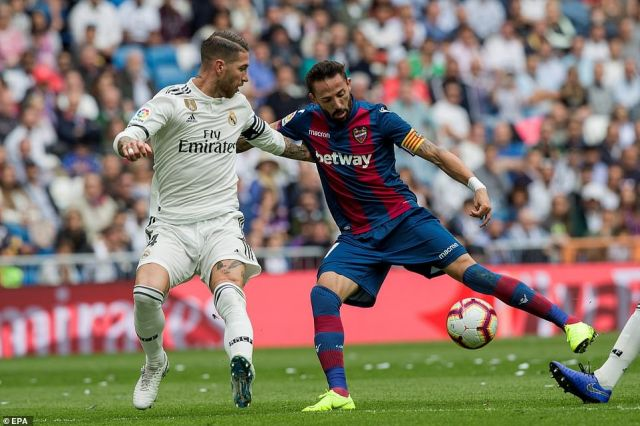 Real captain Ramos battles for possession with Morales during the first half of the La Liga encounter