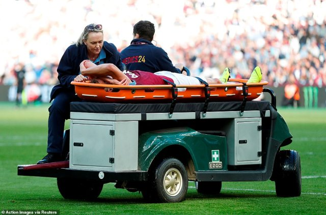 Pitch-side medics tend to the Irons attacker as he is driven off the pitch and taken down the tunnel to be assessed