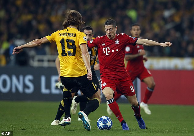 Bayern Munich striker Robert Lewandowski is challenged by AEK's Dmytro Chygrynskiy
