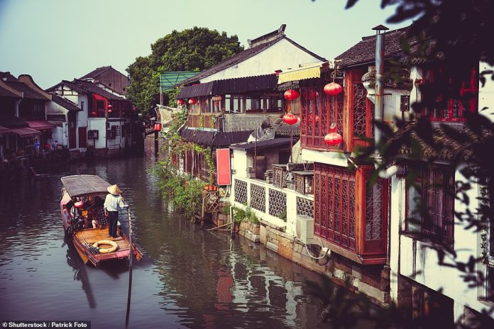 A traditional boat floats along the historic buildings lining a canal in Shanghai. These days the boats are popular with tourists
