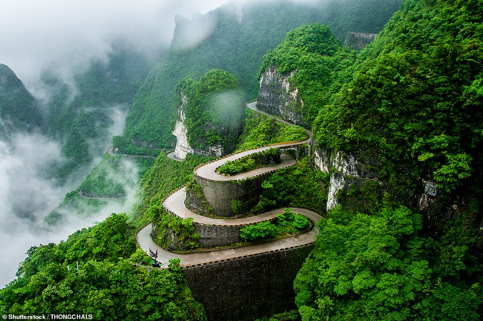 Wispy clouds hang over a winding road that leads up one of the hills in the stunning Tianmen Mountain National Park. The mountain itself has been named one of the most scenic in China