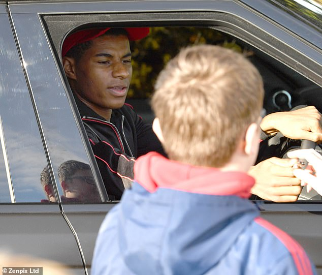 Marcus Rashford signs autographs for Manchester United fans as he arrives for training
