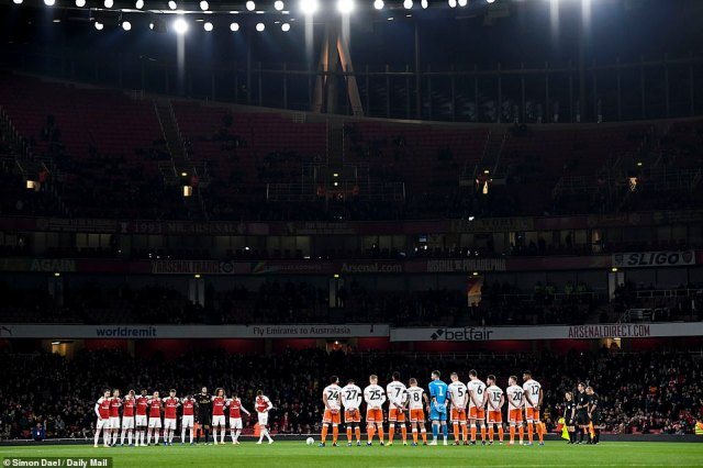 Arsenal and Blackpool players observe a minute's silence for victims of a helicopter crash at Leicester's King Power Stadium