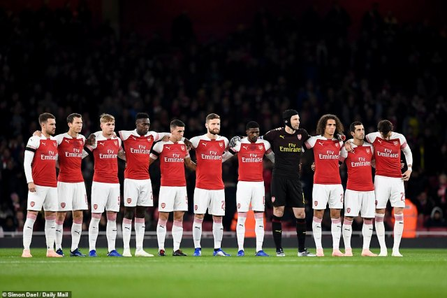 Arsenal players respect the minute's silence held for the five people killed in Saturday's helicopter crash in Leicester