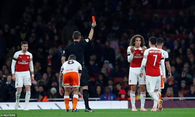 Matteo Guendouzi looks confused as he is sent off by referee David Coote after receiving his second yellow card of the night