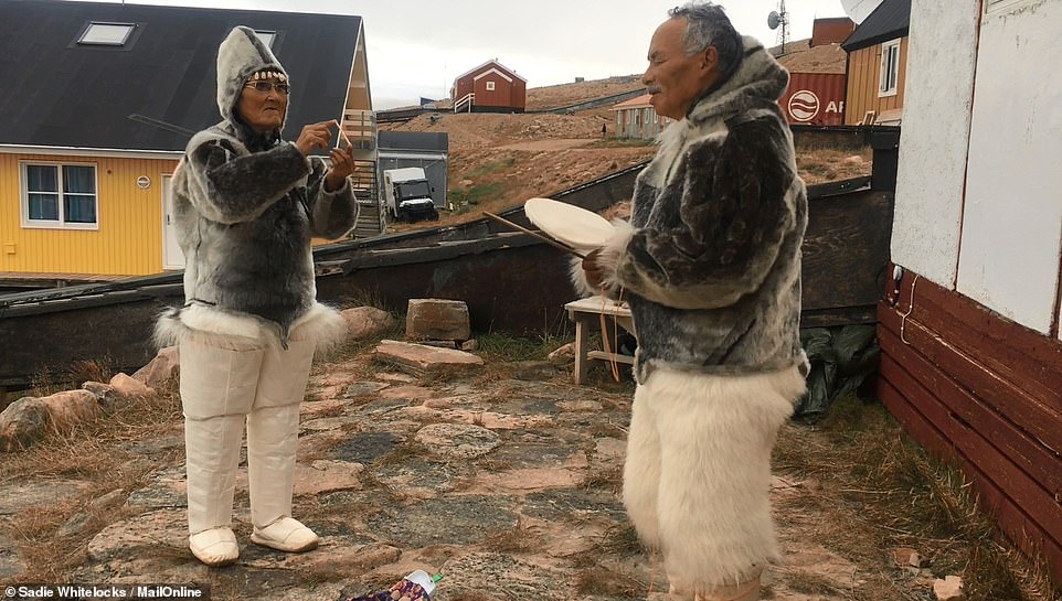 A local man and woman perform a traditional dance with sealskin jackets in front of the small museum in Qaanaaq, providing the ultimate protection from the cold