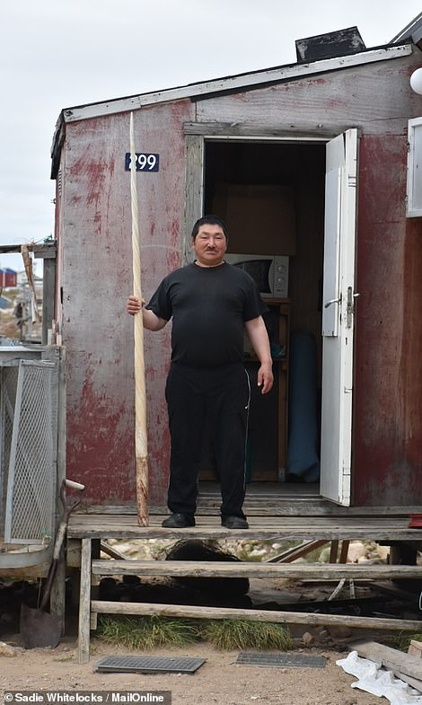 A resident of Qaanaaq shows his huge narwhal tusk