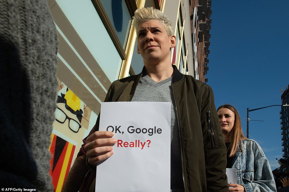 A New York Google employee carries a sign that says, 'OK, Google Really?' while walking out in the global protest on Thursday