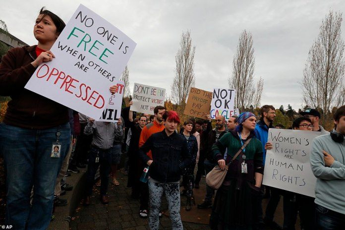 """Google employees in Seattle, Washington wear signs saying, """"Nobody is free when others are oppressed"""" and """"Has the payoff been worth it?"""" during the Global Walkout on Thursday"""