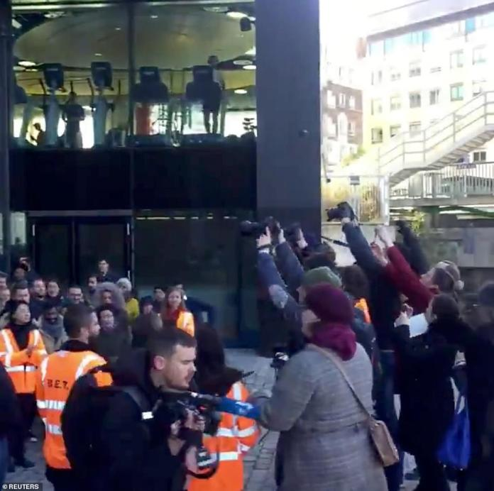 People in orange vests are seen standing among the crowd, as photographers document the Google walkout in Dublin