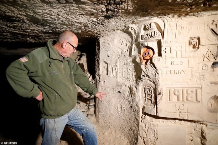 Gilles Chauwin, President of the Chemin des Dames Association and avid WW1 fan, points to American graffiti in the Froidmont quarry