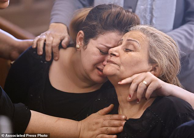 Relatives of the killed Coptic Christians grieve during their funeral in the Church of the Great Martyr Prince Tadros in Minya, Egypt, Saturday, November 3, 2018. The Coptic Orthodox Church in Egypt and the Home Office say that Islamic militants raid three buses of Christian pilgrims have gone to a remote desert monastery south of the Egyptian capital of Cairo, where at least seven people were killed and a dozen more injured. (AP Photo / Amr Nabil)