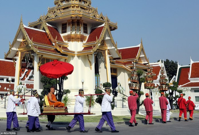 A monk attends a procession with royal soldiers at the temple where the funeral of Vichai Srivaddhanaprabha wants to take place