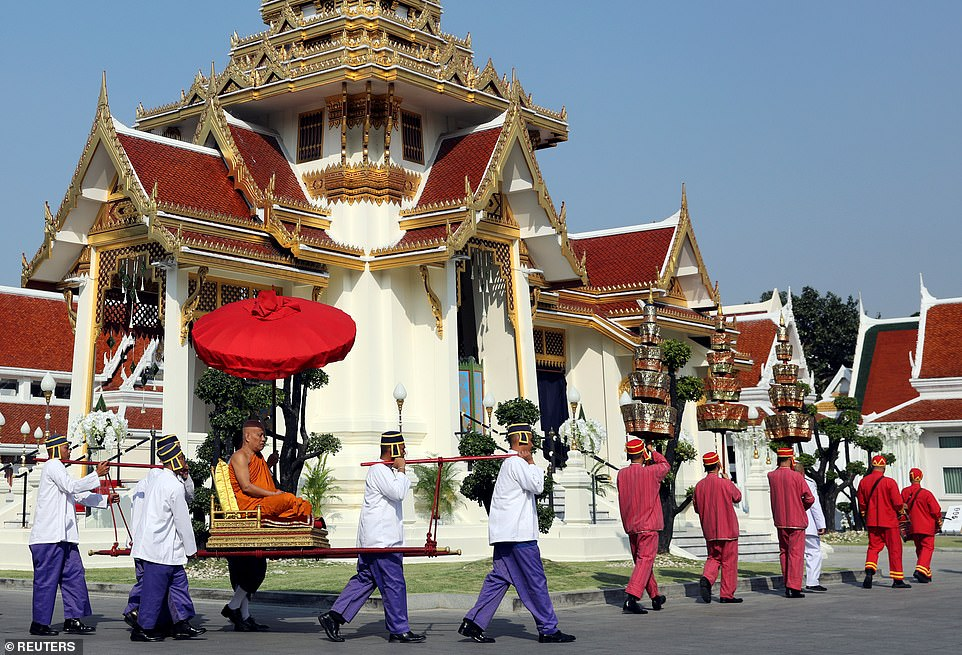 A monk attends a procession with royal soldiers in the temple where the funeral of Vichai Srivaddhanaprabha will take place