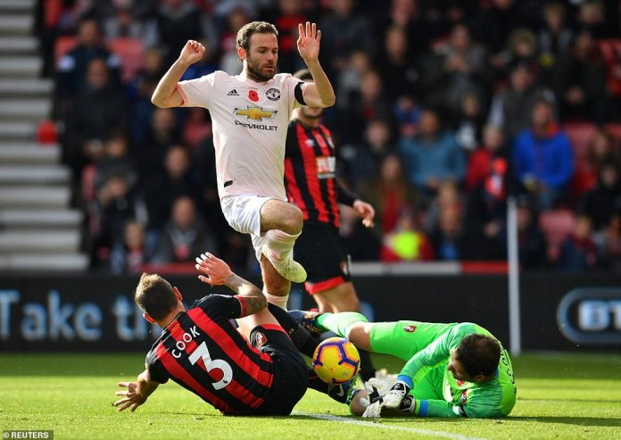 Bournemouth's Steve Cook and Asmir Begovic clash as they desperately try to keep United's Mata off the ball