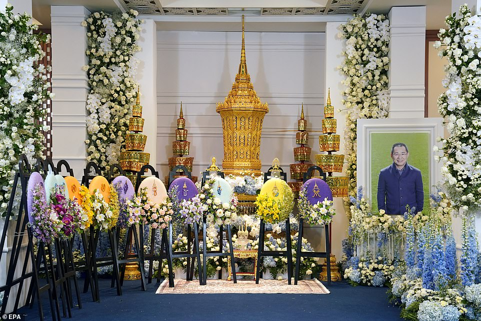 A photo of Leicester's late Thai chairman (R) is set up during his funeral next to an octagonal urn and flowers