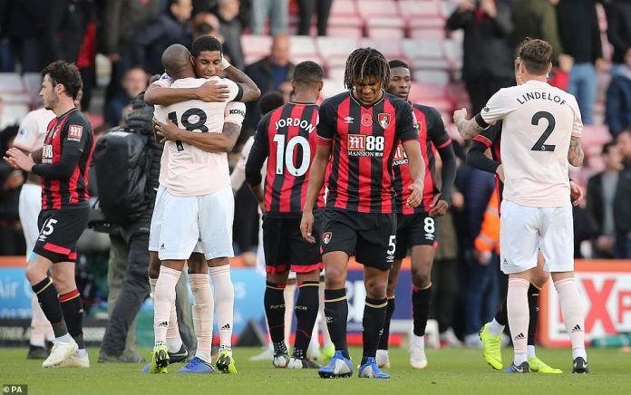 Bournemouth's Nathan Ake looks downcast full time as Manchester United's players celebrate their late victory around him