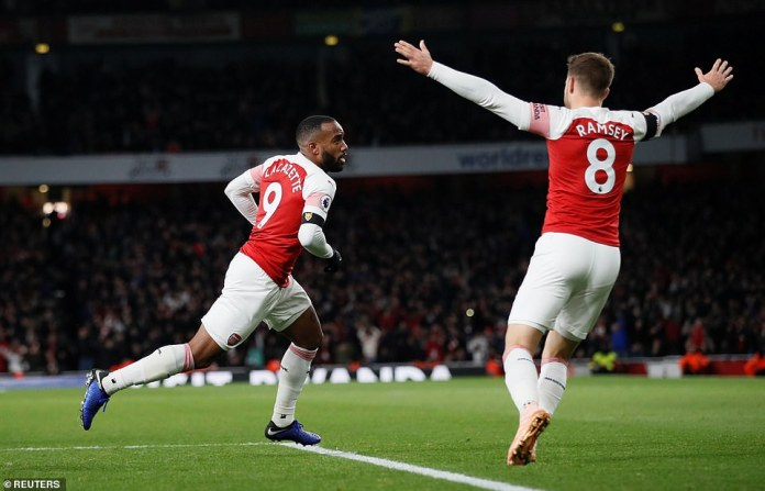 Aaron Ramsey raises his arms solemnly as Lacazette finds the net back for Arsenal on Saturday night