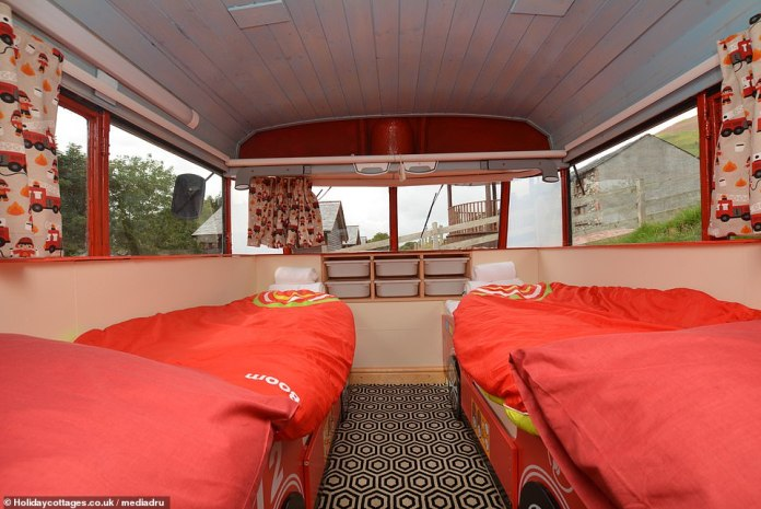 The second bedroom on the ground floor has two beds with bed frames for fire engines and curtains for children with a fire engine