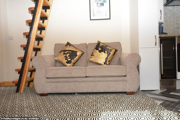 The lounge in the converted fire engine has a comfortable sofa and a ladder that leads guests to the master bedroom