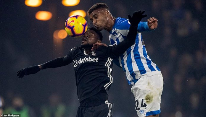 Steve Mounie fights in the air with Fulham's André-Frank Zambo Anguissa at John Smith's Stadium