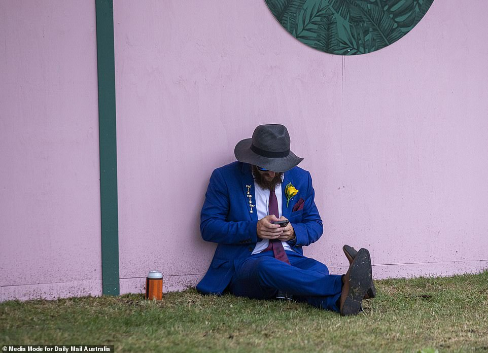 A man in a bright blue suit leans against a pink wall as he finishes off his drink at the event