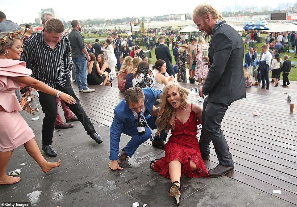 The wet weather created slippery conditions for revellers. Friendly racegoers attempt to help a woman up after the big race