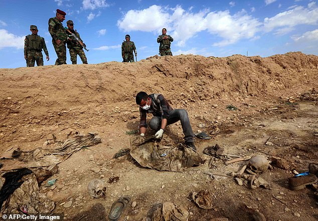Iraqi forces inspect a mass grave full of Yazidi victims in the Sinjar area in February 2015