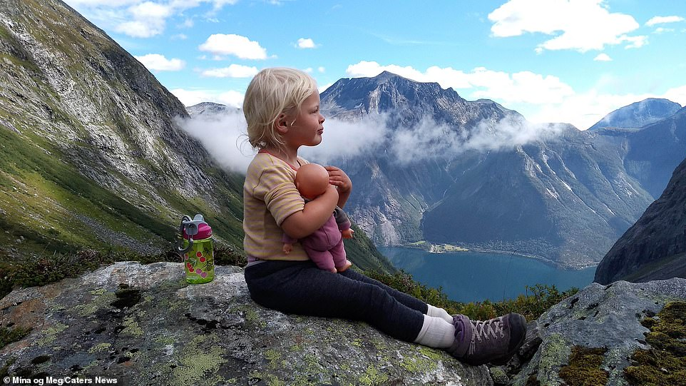 Mina cuddles her doll on a Norwegian summit. Not only does Alex have to take the usual supplies, he also has to bring diapers, toys and storybooks