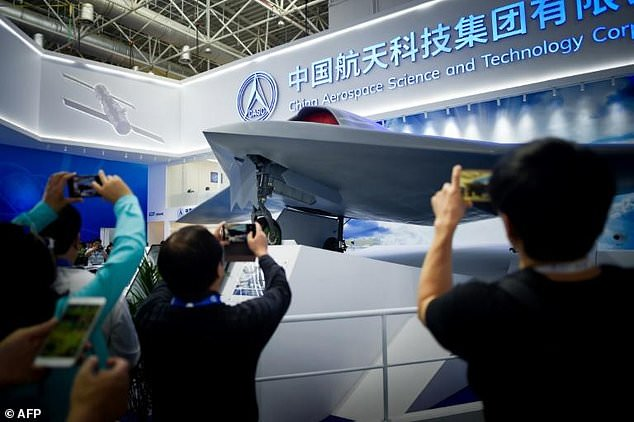 Visitors to the Airshow China take pictures of CH-7, China's newest stealth combat drone